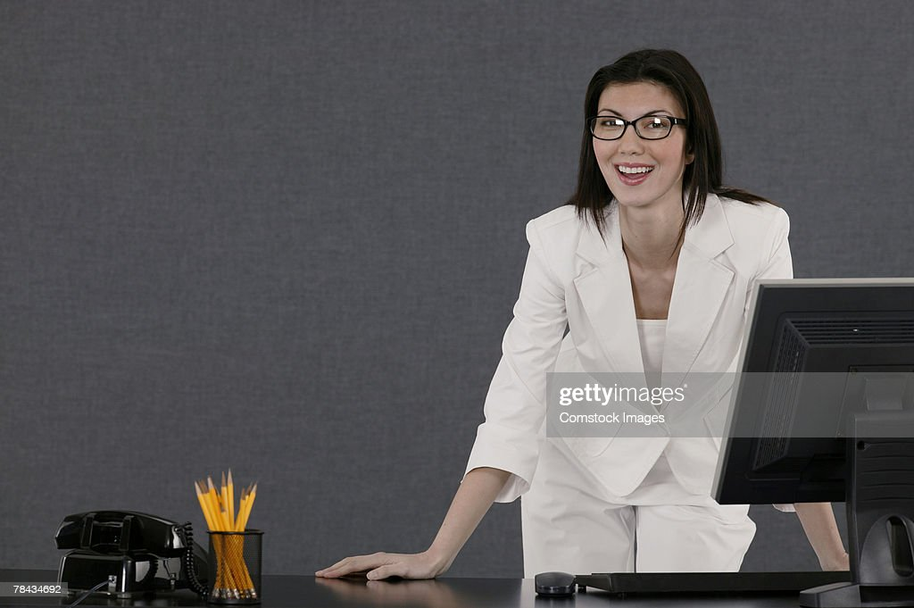Businesswoman standing at desk smiling : Stockfoto