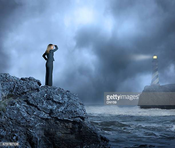 Businesswoman standing at edge of water looking towards a lighthouse