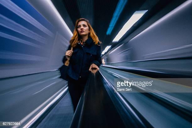 Businesswoman standing at escalator