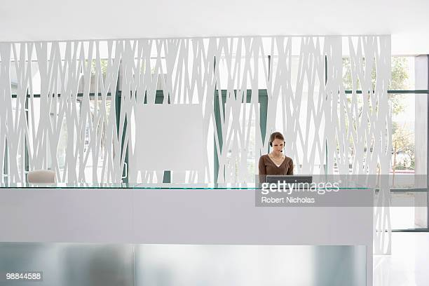businesswoman standing at office reception desk - 受付 ストックフォトと画像