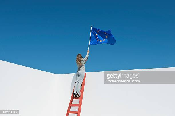 Businesswoman standing at top of ladder, holding European Union flag