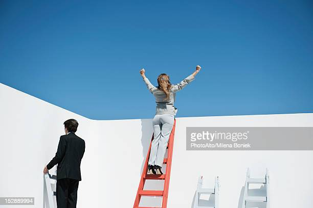 Businesswoman standing at top of ladder with arms raised in air