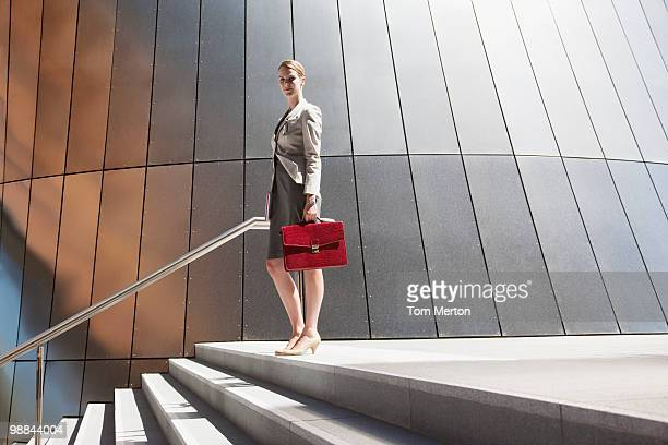 businesswoman standing at top of steps outdoors - briefcase stock photos and pictures
