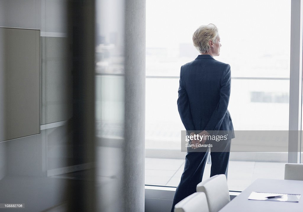 Businesswoman standing at window in office : Stock Photo