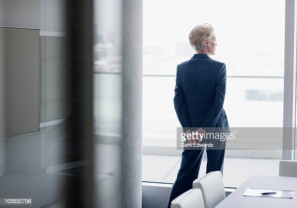 businesswoman standing at window in office - zakenvrouw stockfoto's en -beelden