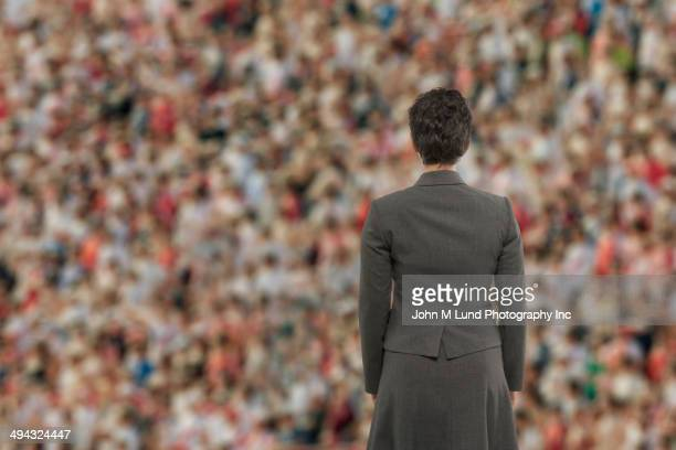 businesswoman standing before crowd - candidate stock pictures, royalty-free photos & images