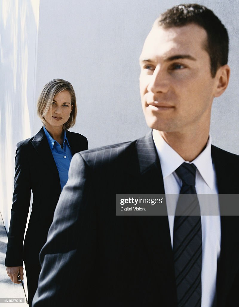 Businesswoman Standing Behind a Businessman : Stock Photo
