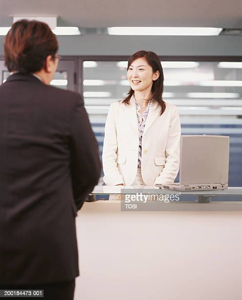 Businesswoman standing behind reception desk, talking to businessman