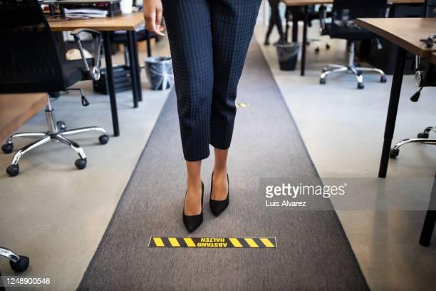 businesswoman standing behind social distancing signage on floor - anweisungen konzepte stock-fotos und bilder