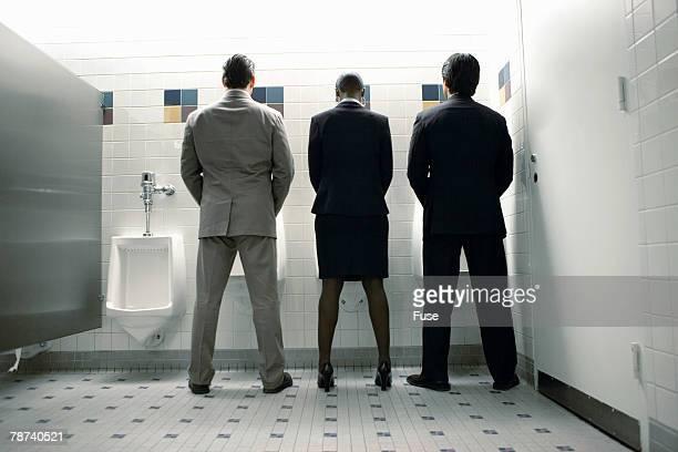 Businesswoman Standing Between Businessman at Urinals
