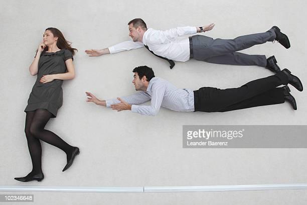 businesswoman standing, businessmen flying in superman pose, side view - 横向きに寝る ストックフォトと画像