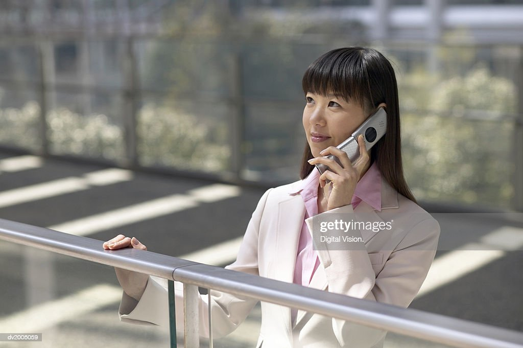 Businesswoman Standing by a Railing and Using a Mobile Phone : Stock Photo