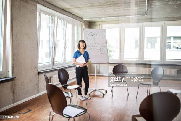Businesswoman standing by flip chart in office