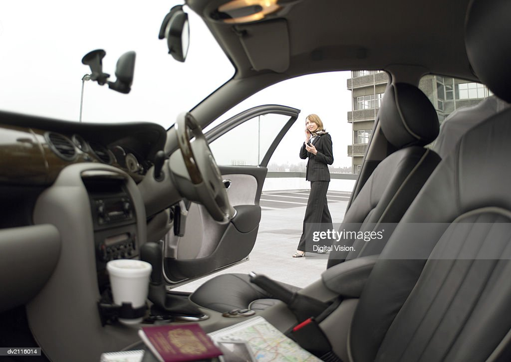 Businesswoman Standing by Her Car and Using a Mobile Phone : Stock Photo