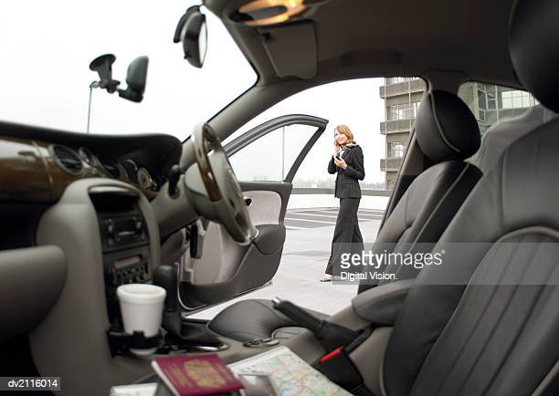 Businesswoman Standing by Her Car and Using a Mobile Phone