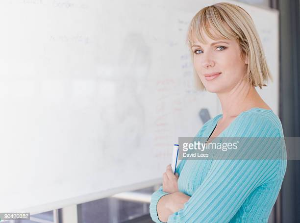Businesswoman standing by white board, smiling