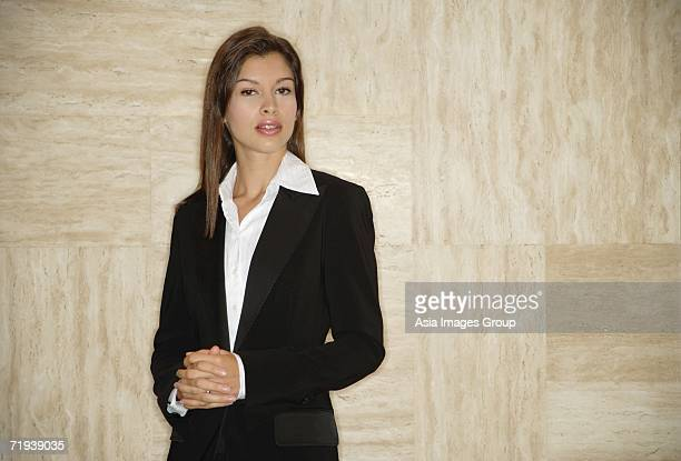 Businesswoman standing, hands clasped, looking at camera