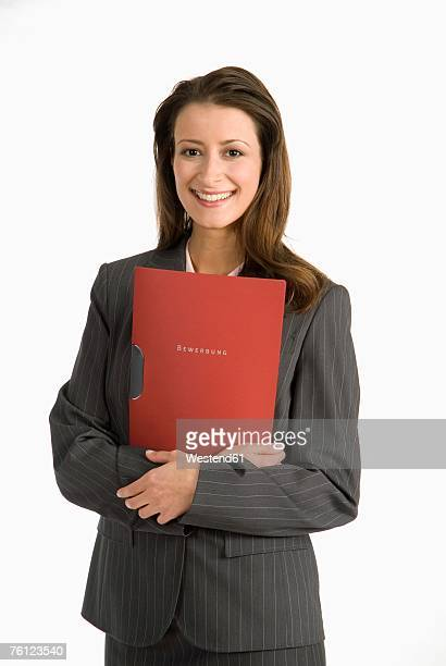 Businesswoman standing, holding file, smiling, portrait