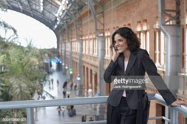 businesswoman standing in a balcony and using a mobile phone - personas en el fondo fotografías e imágenes de stock