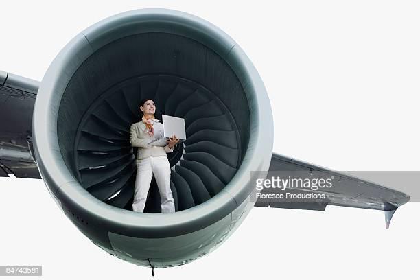 Businesswoman standing in airplane engine