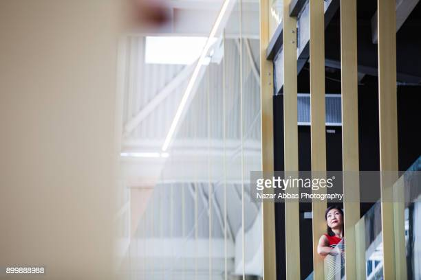 Businesswoman standing in balcony of office building and looking outside.