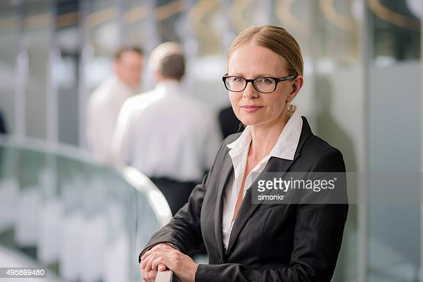 businesswoman standing in corridor - thick rimmed spectacles stock photos and pictures