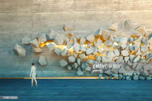 empresária em frente a parede quebrando - obstruir - fotografias e filmes do acervo