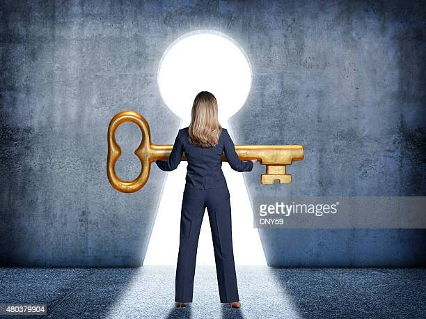 Businesswoman standing in front of keyhole holding a large key