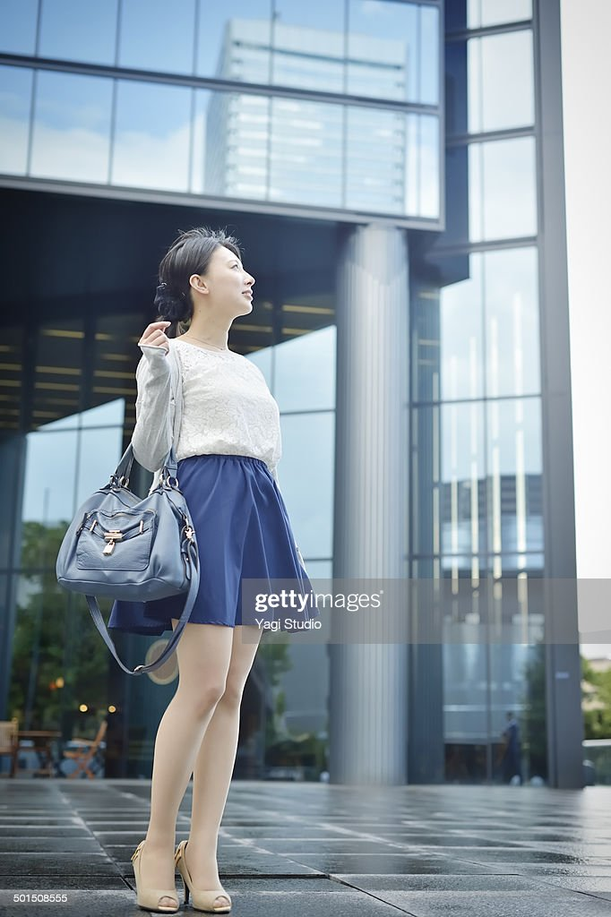 Businesswoman standing in front of the building : Stock Photo