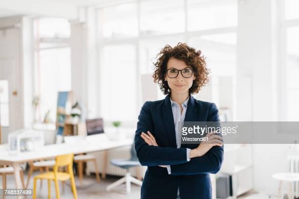 businesswoman standing in her office with arms crossed - geschäftsfrau stock-fotos und bilder