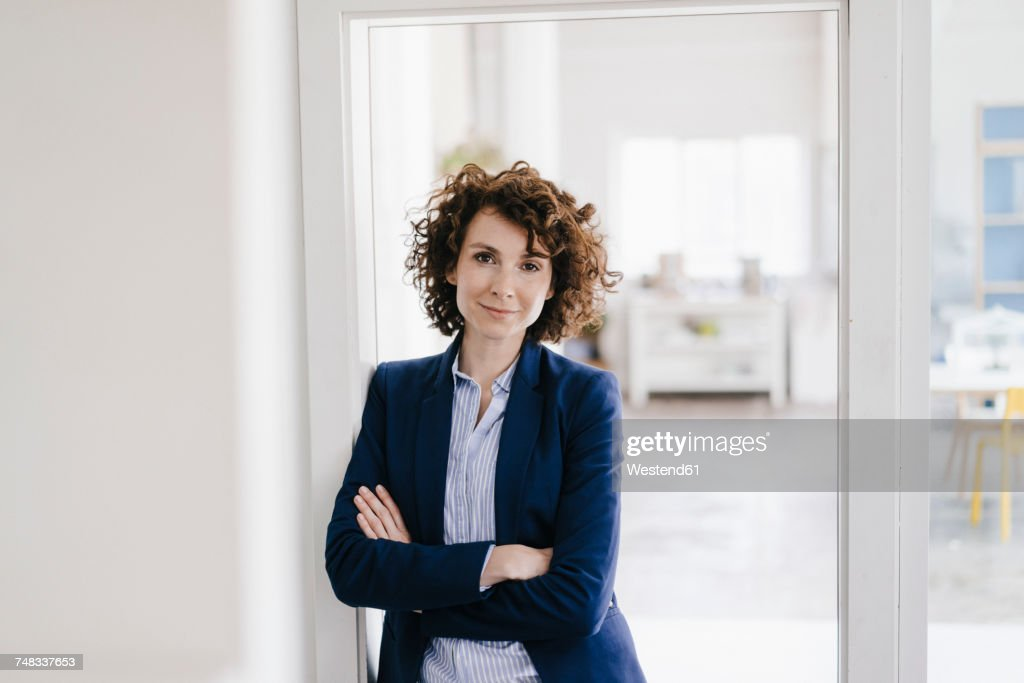 Businesswoman standing in her office with arms crossed : Stock Photo
