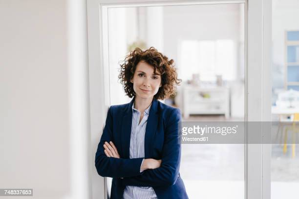 businesswoman standing in her office with arms crossed - mid adult stock-fotos und bilder