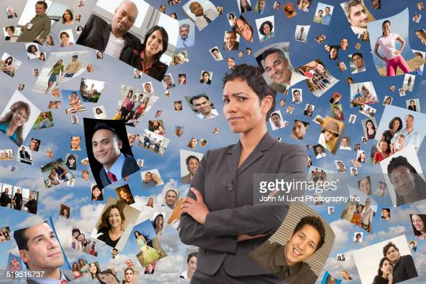Businesswoman standing in images of faces floating in sky