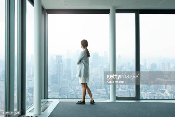 businesswoman standing in large conference room and looking out of windows - big white women stock photos and pictures
