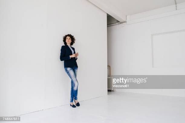 businesswoman standing in loft , leaning against wall - もたれる ストックフォトと画像