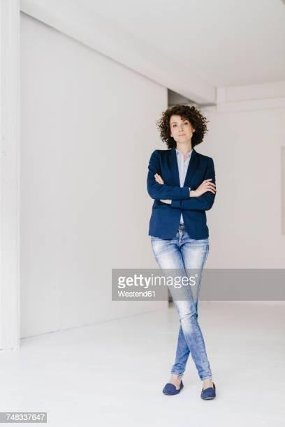 businesswoman standing in loft with arms crossed - arme verschränkt stock-fotos und bilder