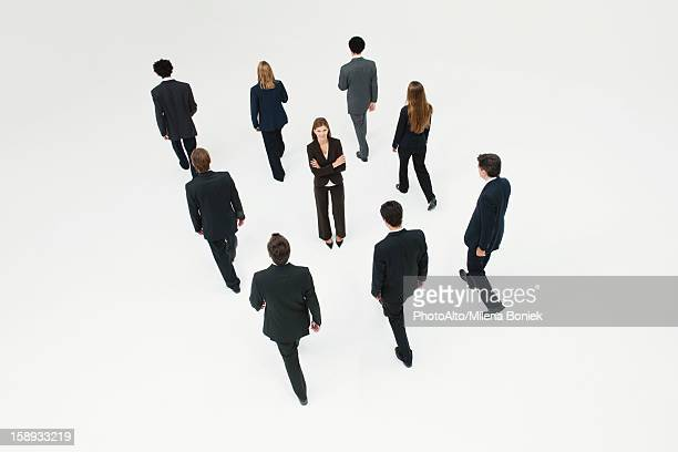 Businesswoman standing in midst of other anonymously dressed business professionals