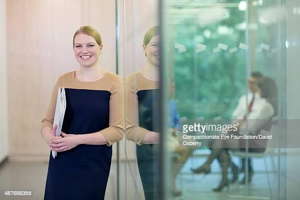 Businesswoman standing in modern office hallway