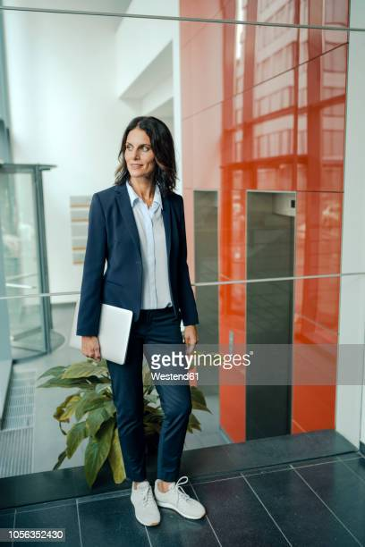 businesswoman standing in office building, holding laptop - pant suit stock pictures, royalty-free photos & images