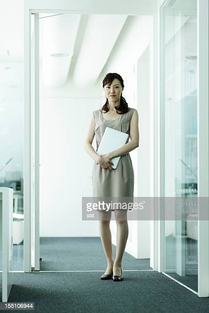 Businesswoman standing  in office hallway