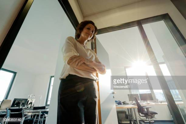 businesswoman standing in office, with arms crossed, looking down - vista de ângulo baixo - fotografias e filmes do acervo