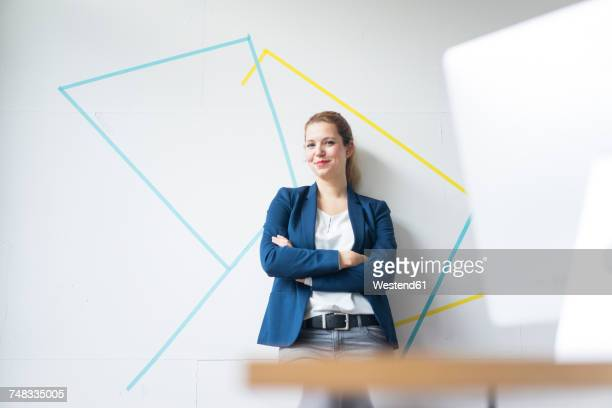 businesswoman standing in office with arms crossed - designer professionista foto e immagini stock