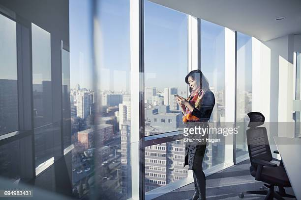 Businesswoman standing in office with mobile phone