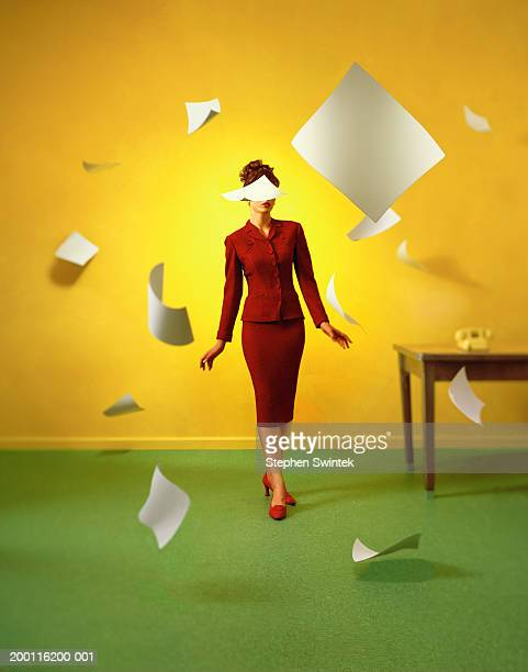 Businesswoman standing in room, surrounded by falling pieces of paper