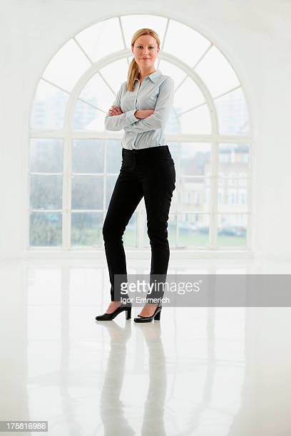 businesswoman standing in sparse white room - trousers stock pictures, royalty-free photos & images