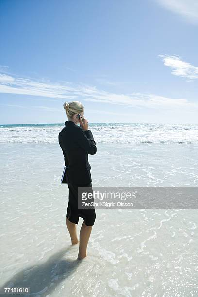Businesswoman standing in surf, holding agenda and using cell phone