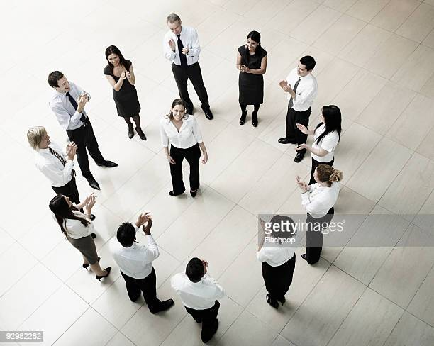businesswoman standing in the centre of a circle - femme entre deux hommes photos et images de collection