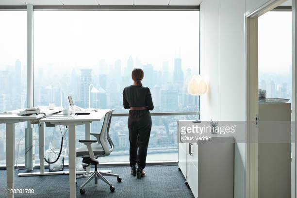 businesswoman standing inside office and looking out of big window with beautiful view of skyline - looking at view stock-fotos und bilder