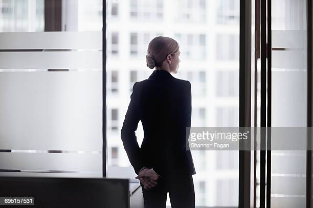 businesswoman standing looking out office window - three quarter length stock pictures, royalty-free photos & images