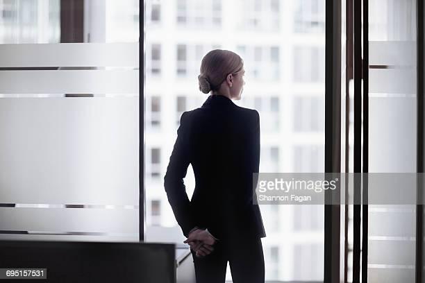 businesswoman standing looking out office window - driekwartlengte stockfoto's en -beelden